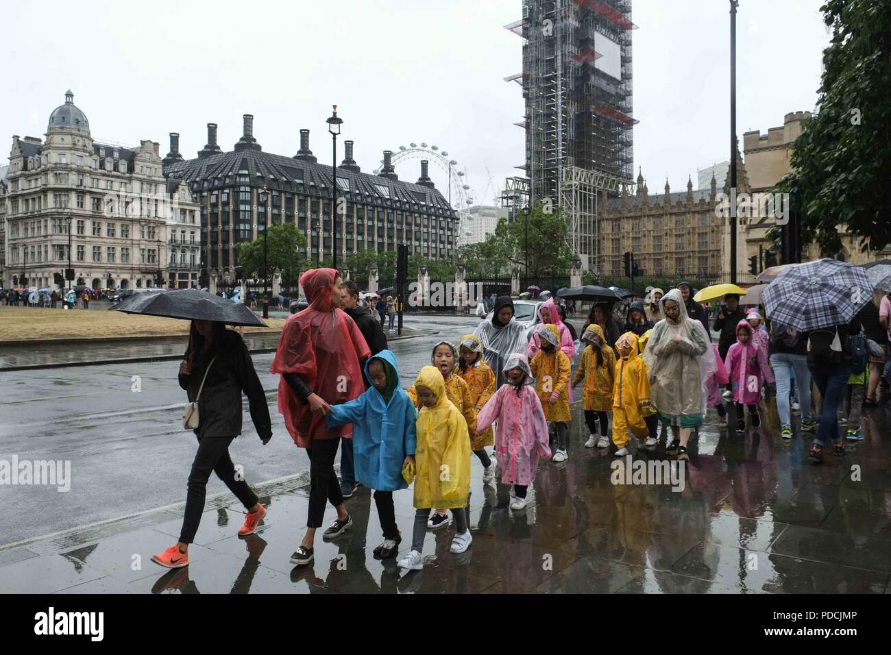 London 9th August 2018:  A group of children wear ponchos in heavy rain . Credit: Claire Doherty/Alamy Live News - Stock Image