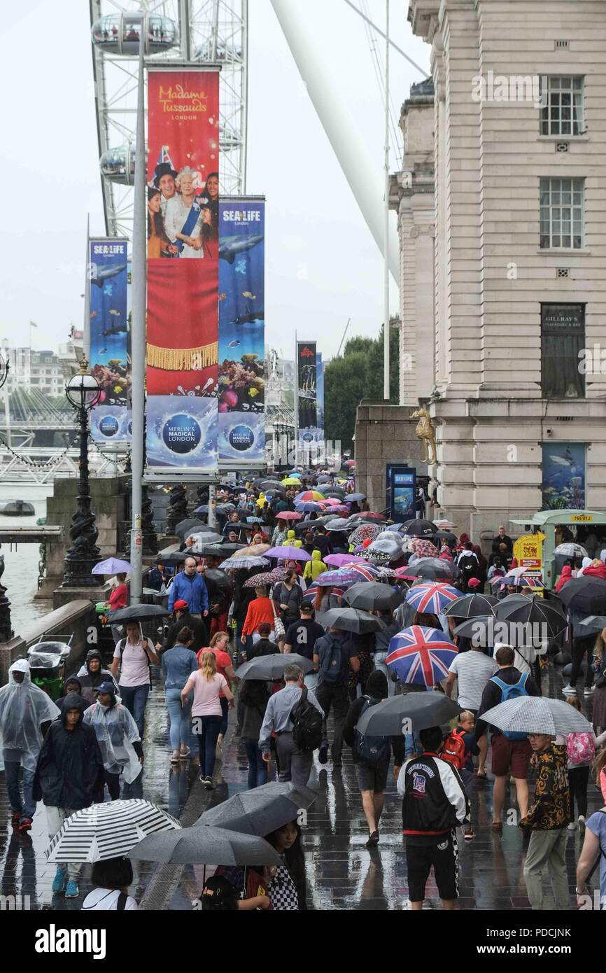 London 9th August 2018:  Crowds of tourists on Westminster pier shelter from the rain under umbrellas. Credit: Claire Doherty/Alamy Live News - Stock Image