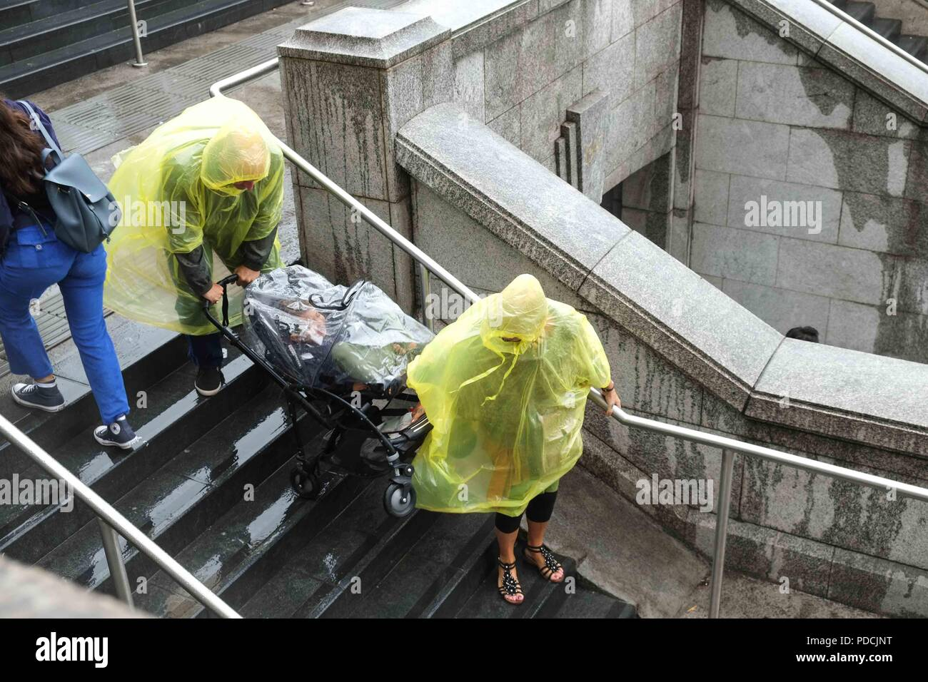 London 9th August 2018:  A couple carry a push chair down a flight of stairs on Westminster Bridge.Credit: Claire Doherty/Alamy Live News - Stock Image