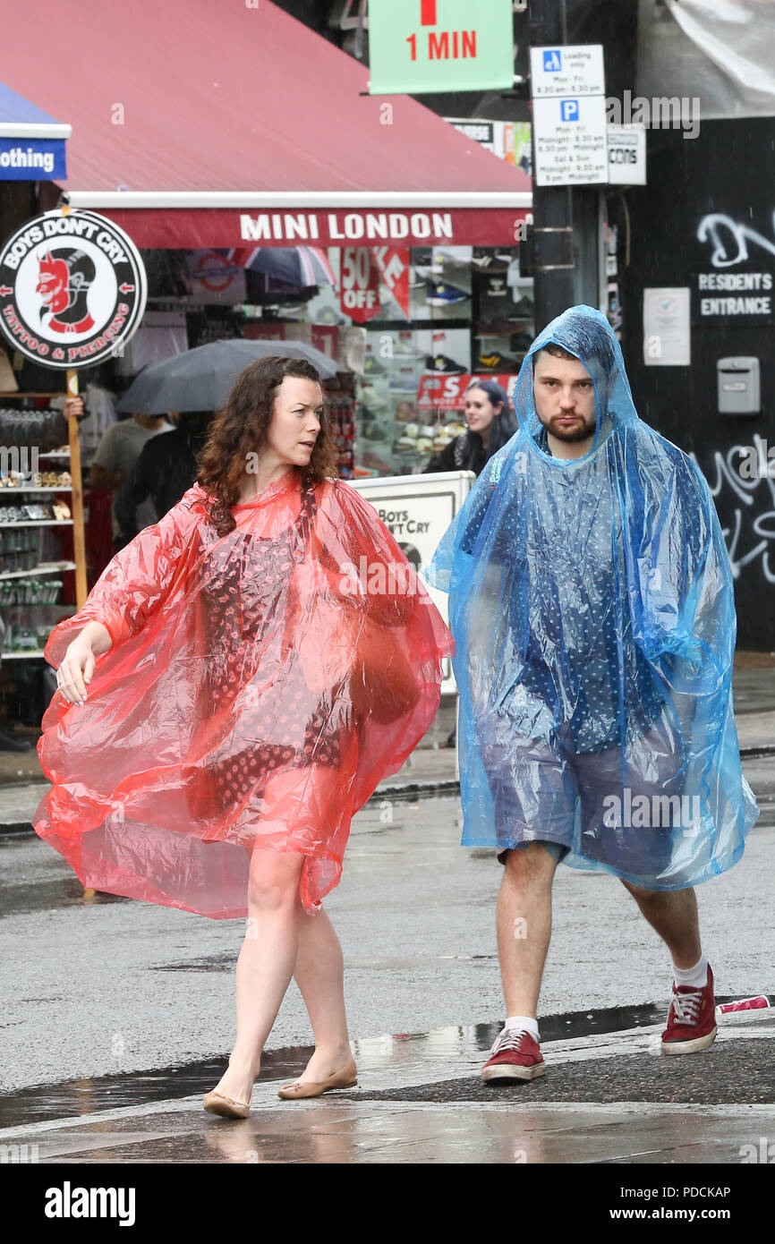 Camden Market. London. UK 9 Aug 2018 - Tourists wearing rain ponchos in Camden Market as rain falls in London after couple of months of the heatwave.  Credit: Dinendra Haria/Alamy Live News - Stock Image