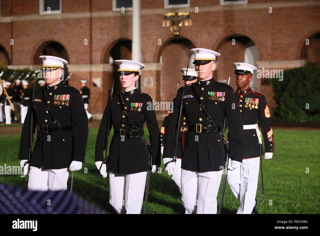 Marines with the Marine Barracks Washington D.C. parade marching staff march across the parade deck during a Friday Evening Parade at the Barracks, Aug. 03, 2018. The guests of honor for the parade were Ms. Ryan Manion, president, Travis Mannion Foundation, and U.S. Marine Corps Col. Tom Manion, retired, chairman emeritus, Travis Manion Foundation. The hosting official was Lt. Gen. Michael G. Dana, director, Marine Corps Staff. - Stock Image