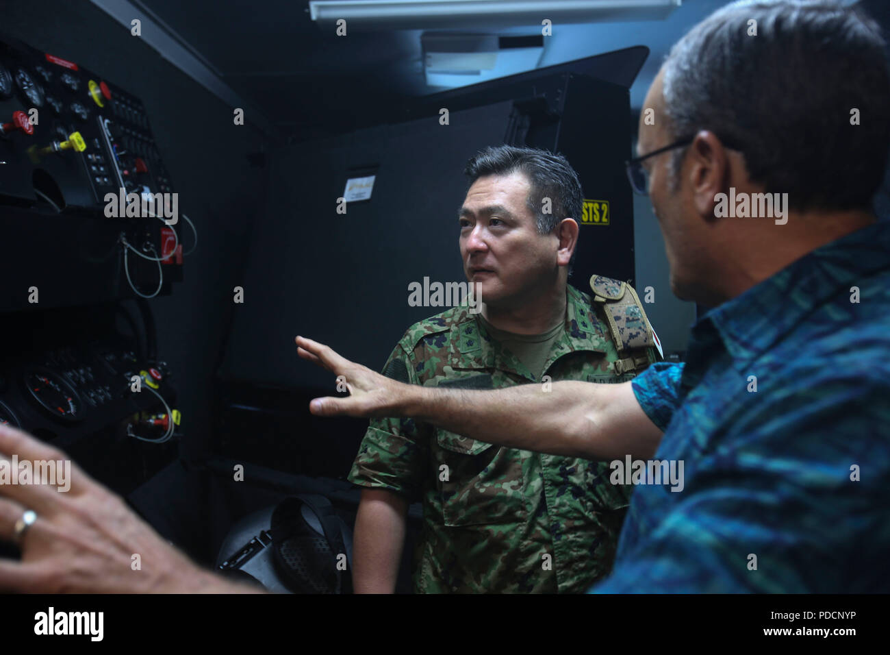Major Gen. Yoshiki Adachi, defense and military attaché, Embassy of Japan, is briefed on the schematics of a controlled driving simulator on Camp Lejeune, N.C., Aug. 3, 2018. Adachi is visiting the Marines and Sailors of II Marine Expeditionary Force to continue to build relationships and understand II MEF's mission and activities in the western hemisphere in regards to its amphibious capabilities and operations. (U.S. Marine Corps photo by Lance Cpl. Samuel Lyden) - Stock Image