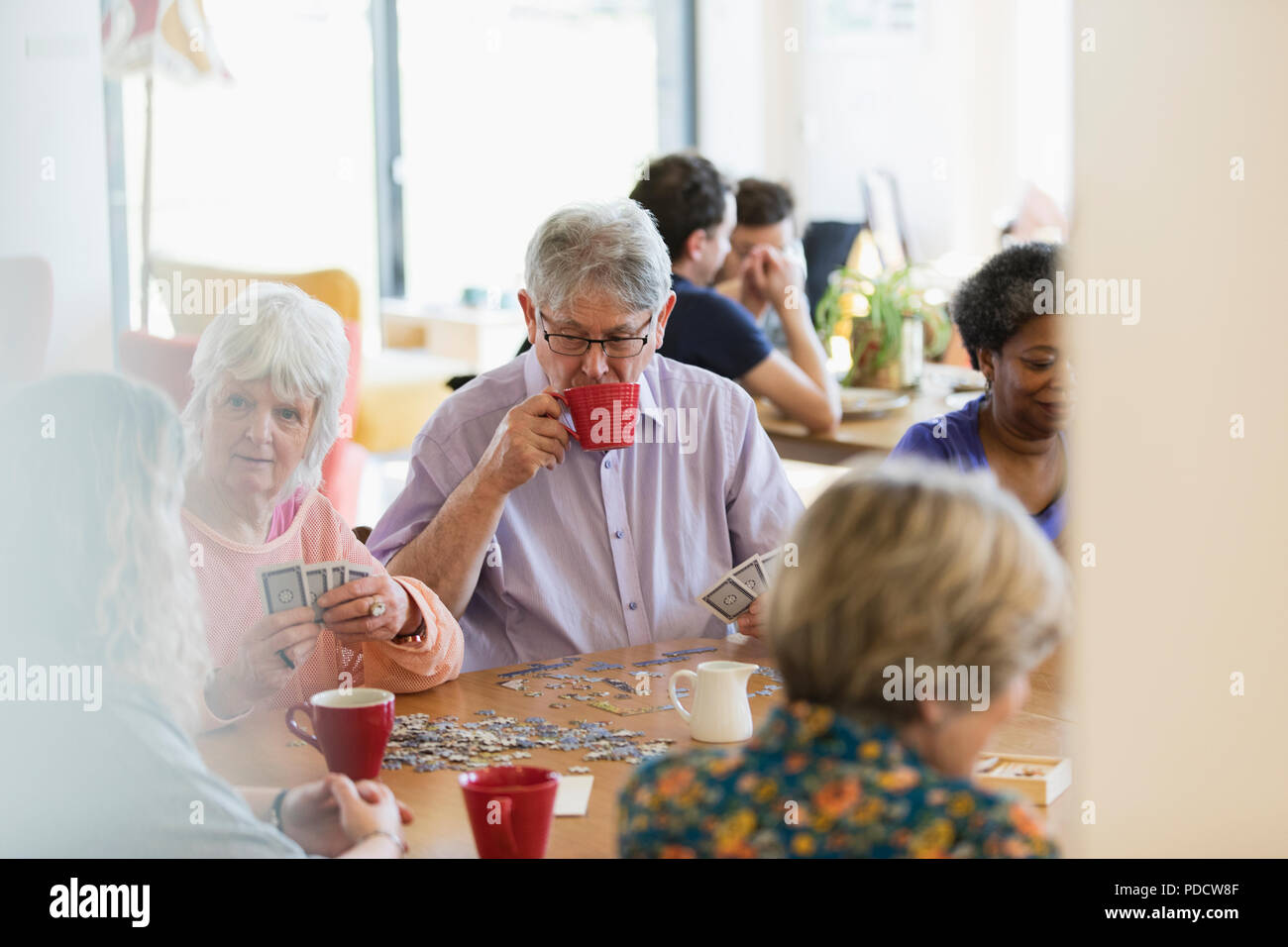 Senior friends playing games and drinking tea at table in community center - Stock Image