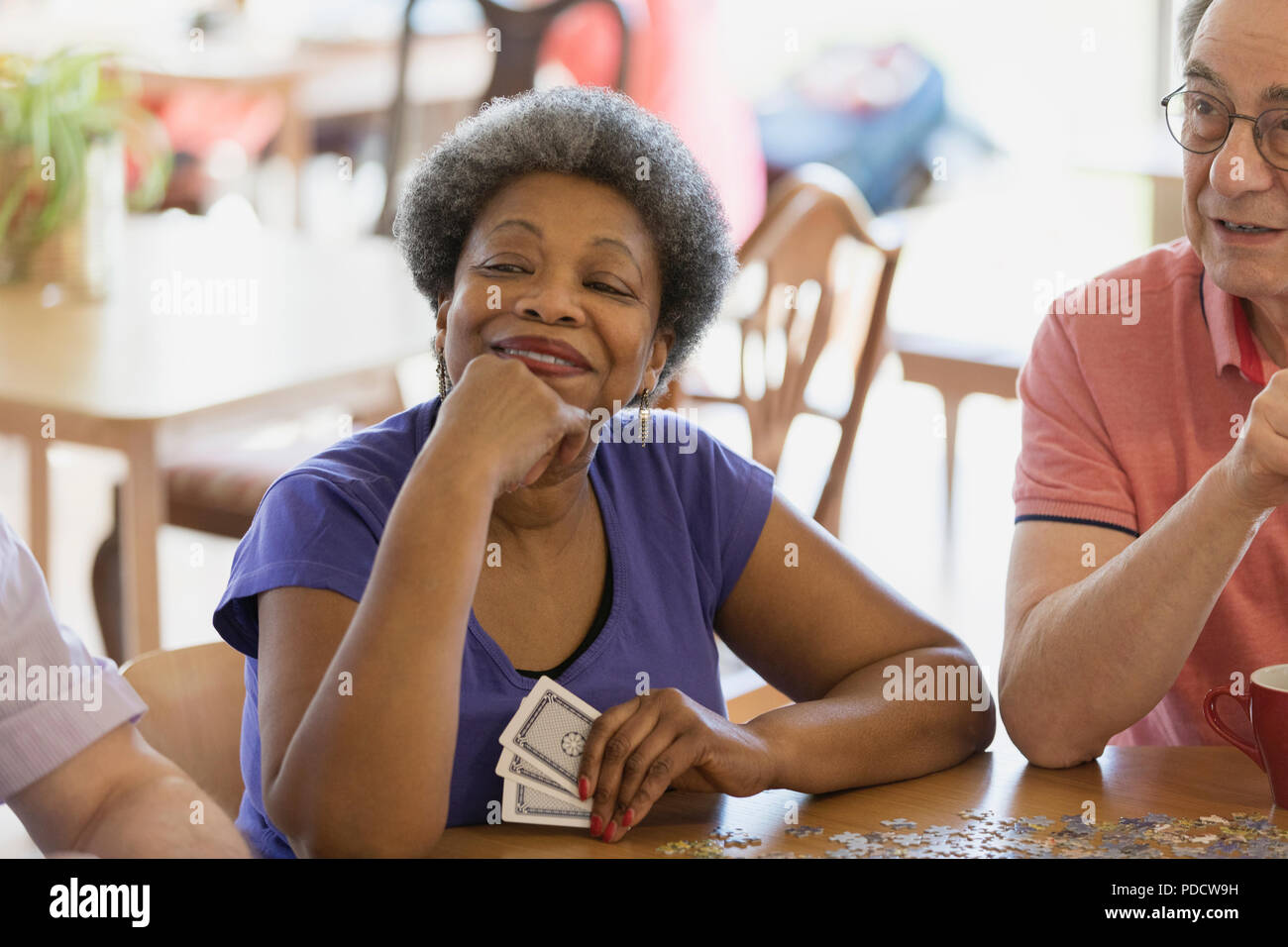 Confident, happy senior woman playing cards with friends in community center - Stock Image