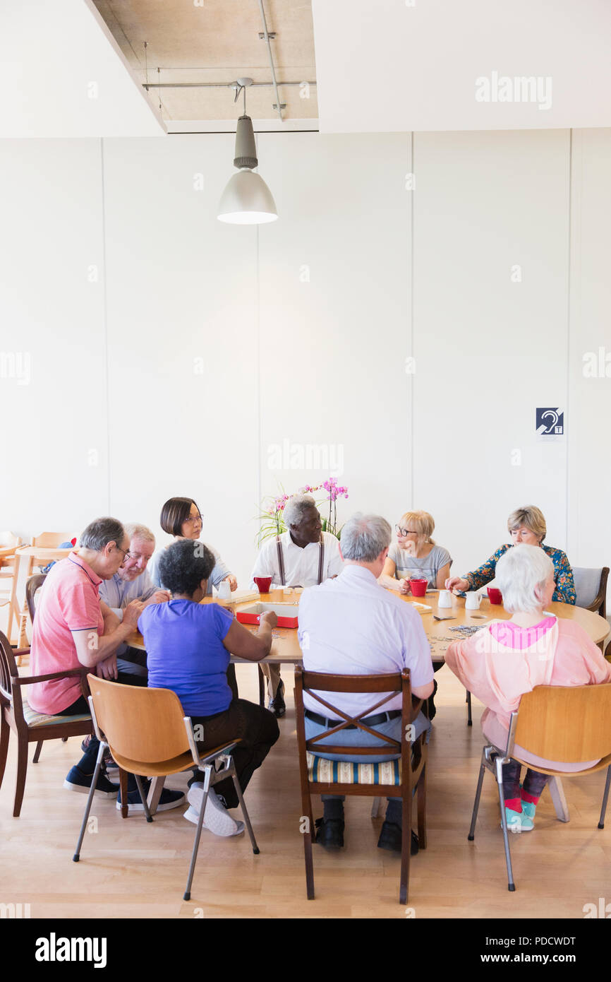 Senior friends playing games at table in community center - Stock Image