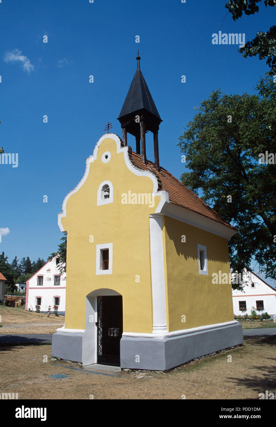 Ochre painted chapel in the historic village of Holasovice in South Bohemia in the Czech Republic - Stock Image