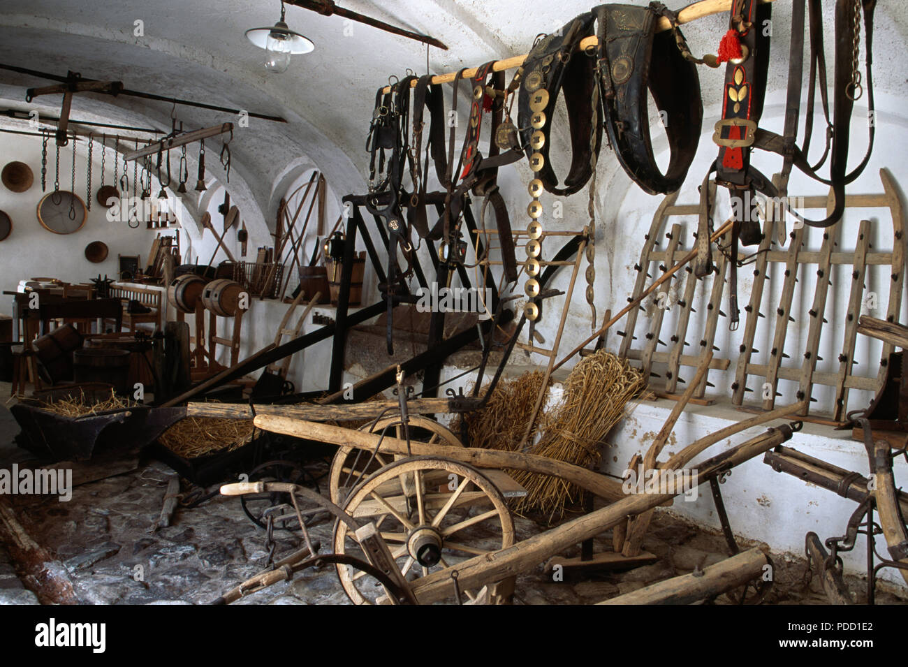 Old wooden carts and horse tack in museum in Holasovice historic village in South Bohemia in Czechoslovakia - Stock Image
