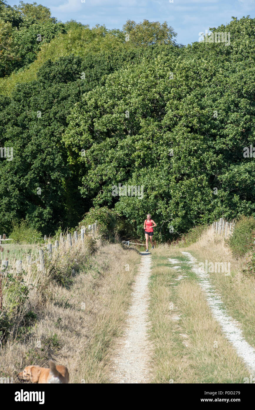 lady running along a country lane keeping fit. - Stock Image