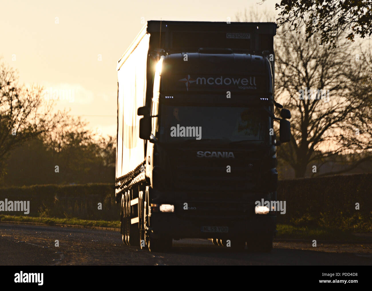 Scania HGV on A-road silhouetted by sun Stock Photo