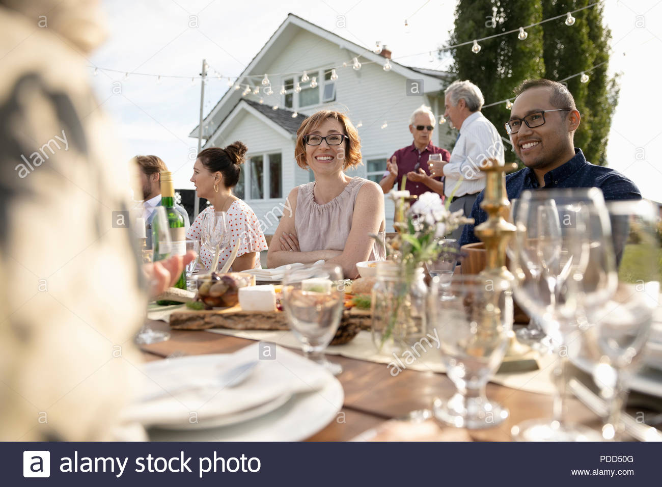 Friends enjoying wedding reception lunch at rural table - Stock Image