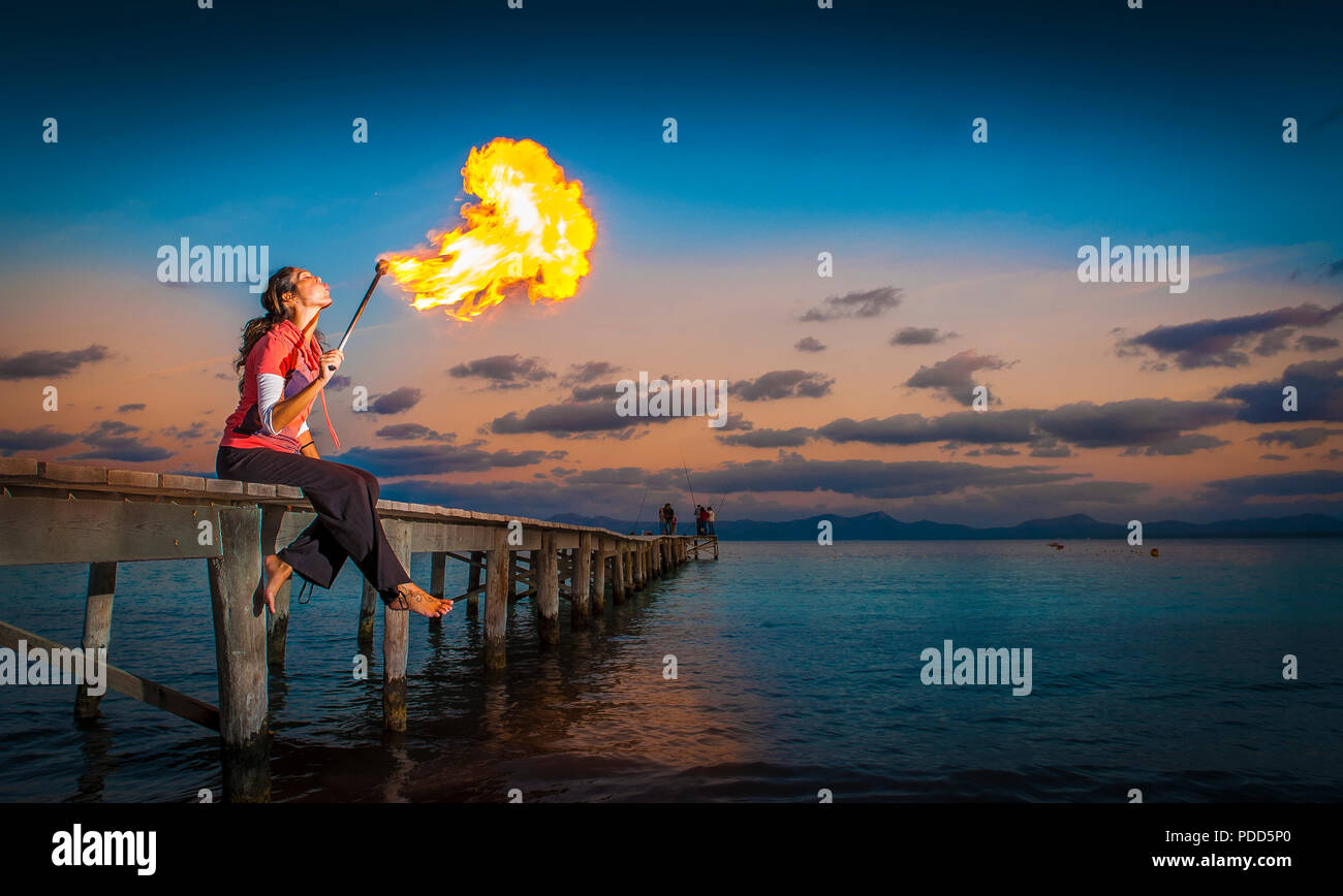 Fire eater sitting on a jetty by the sea. - Stock Image