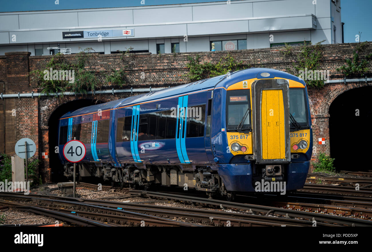 Class 375 passenger train in Southeastern livery travelling past Tonbridge railway station. - Stock Image