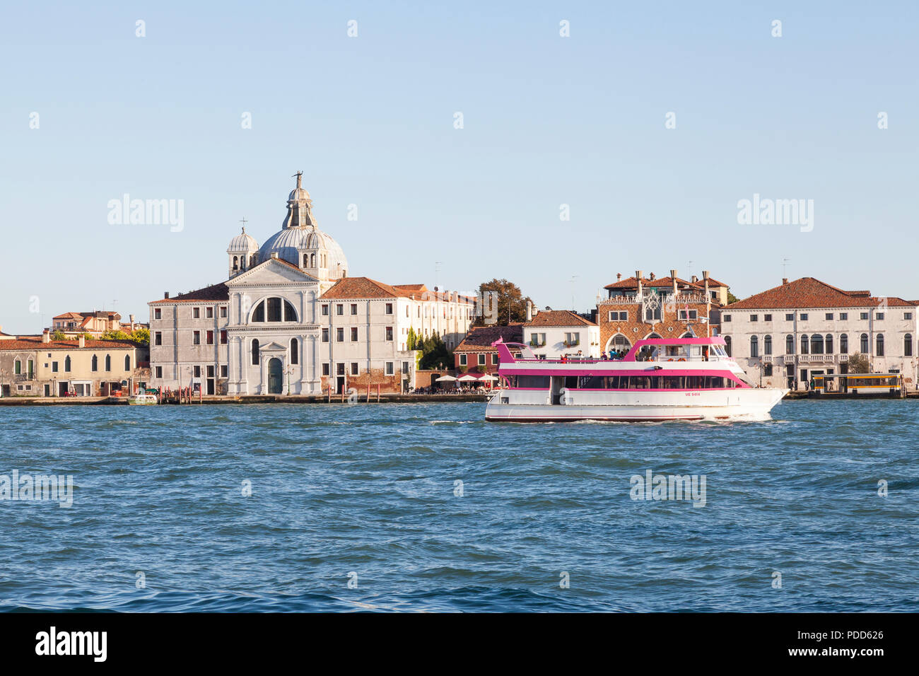 The Pink Venice tour boat, Giudecca Canal, Venice, Veneto, Italy at sunset  passing the Zitelle Church and Tre Oci Exhibition Centre on Giudecca Islan - Stock Image
