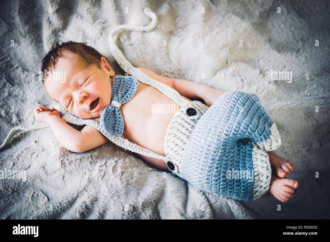 A newborn baby boy sleeping in blue and grey knitted bow tie and trousers - Stock Image