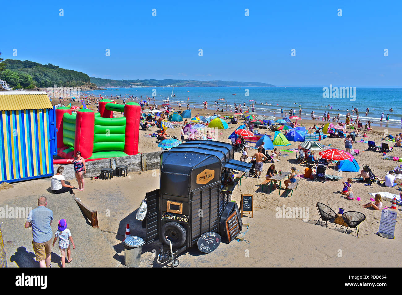 Crowded & busy summertime beach scene at Saundersfoot, Pembrokeshire, with bouncy castle and fast food outlet in foreground - Stock Image