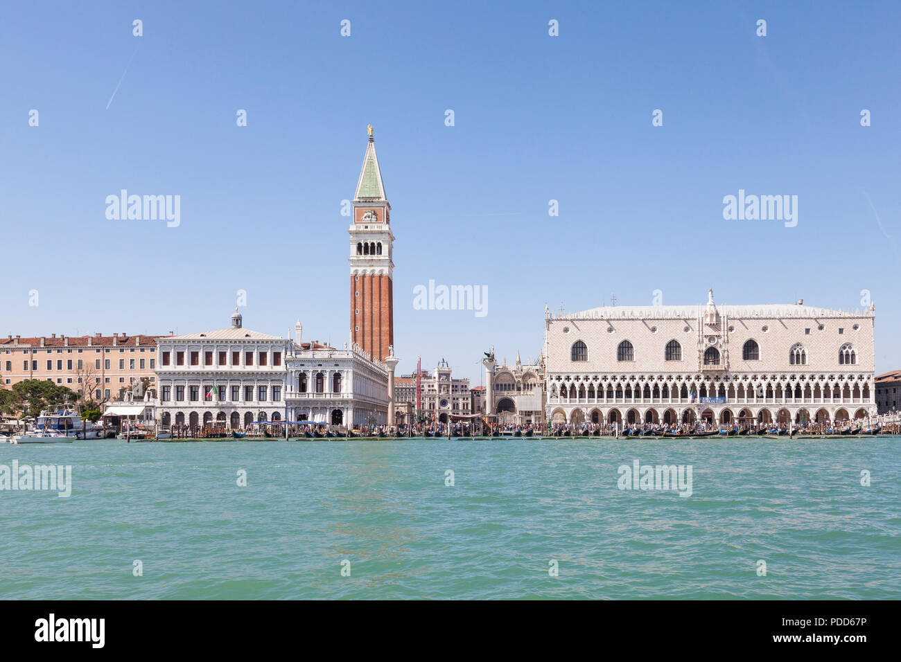 Doges Palace, St Marks Campanile and Marciana Library from the lagoon, Venice, Veneto, Italy with the Clock Tower and crowds of tourists  in summer - Stock Image