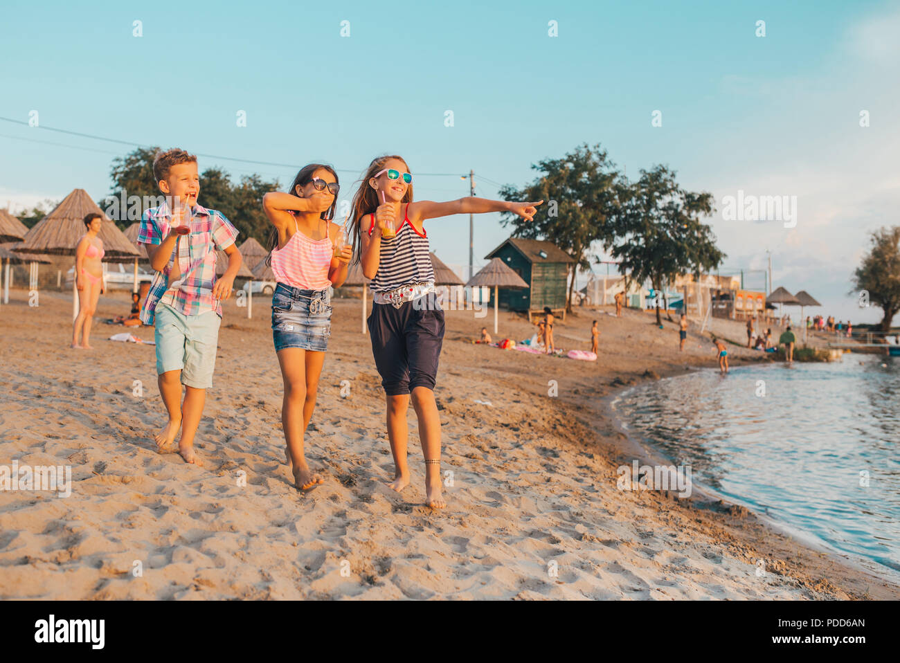 Portrait of happy children having fun while walking on the shore - Stock Image