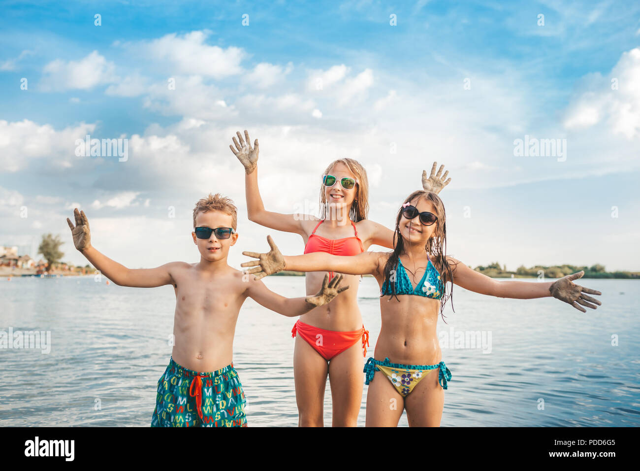 Happy children playing in the sea. Kids having fun outdoors  while spreading their hands and looking at the camera. Summer vacation and healthy lifest - Stock Image