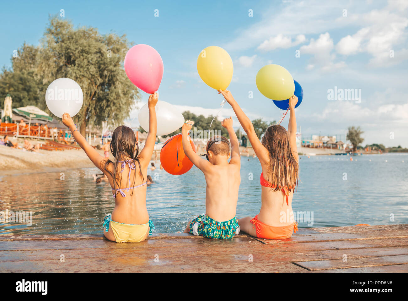 Happy children playing with balloons in the sea. Kids having fun outdoors. Summer vacation and healthy lifestyle concept Stock Photo