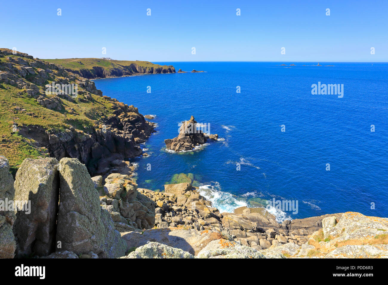 Distant Longships Lighthouse off Land's End from Mayon Cliff on the South West Coast Path, Sennen, Cornwall, England, UK. - Stock Image