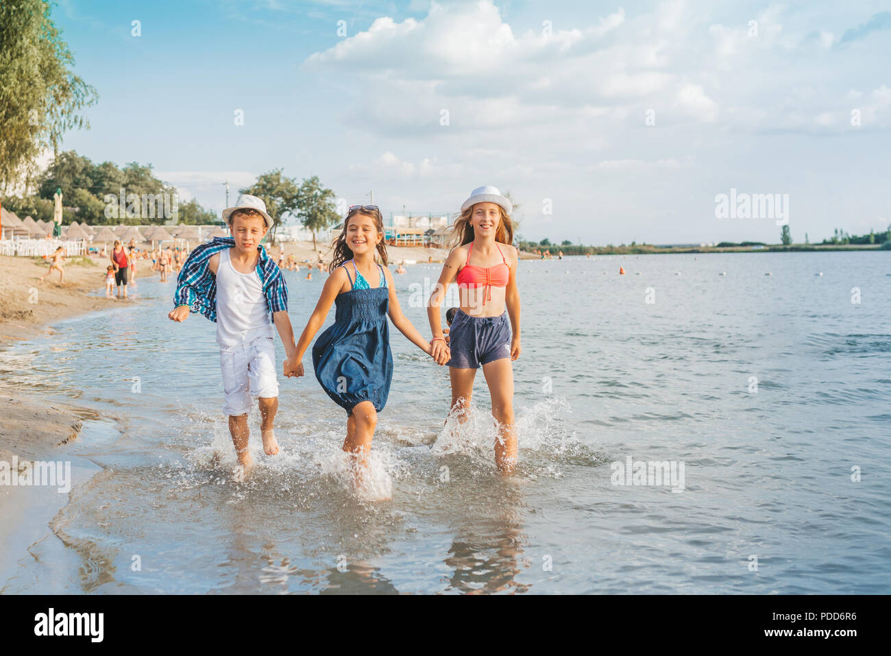 Happy joyful little children playing in the sea, with pleasure splashing the water, enjoying summer holidays on the beach resort, travel and tourism c - Stock Image