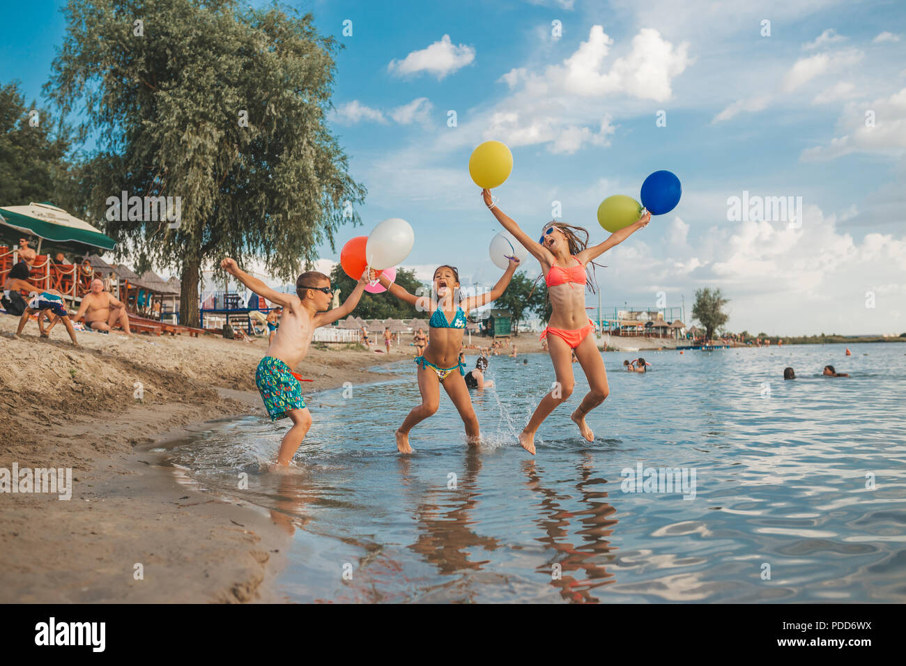 Happy children playing with balloons in the sea. Kids having fun outdoors. Summer vacation and healthy lifestyle concept - Stock Image
