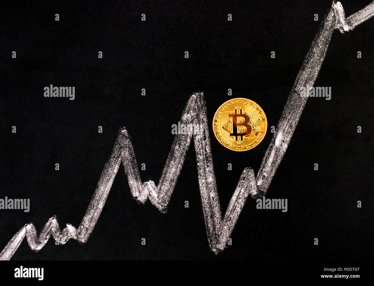 Golden Bitcoin virtual coin on blackboard with chalk drawing graph. Close-up. - Stock Image