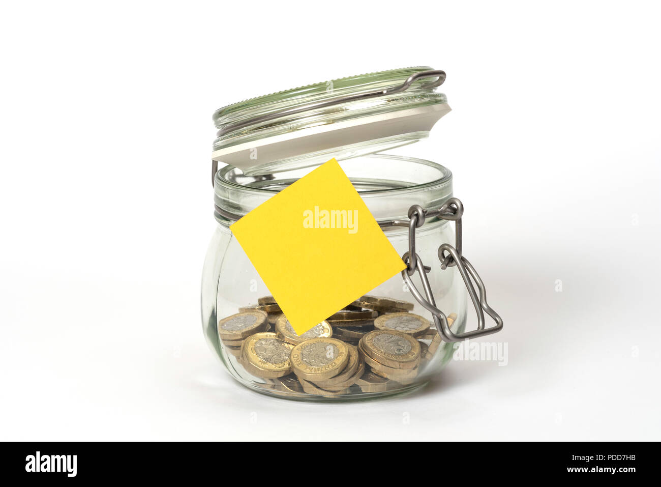 Slush fund: glass clip top Kilner storage jar with British one pound coins and blank yellow stickie post-it note - Stock Image