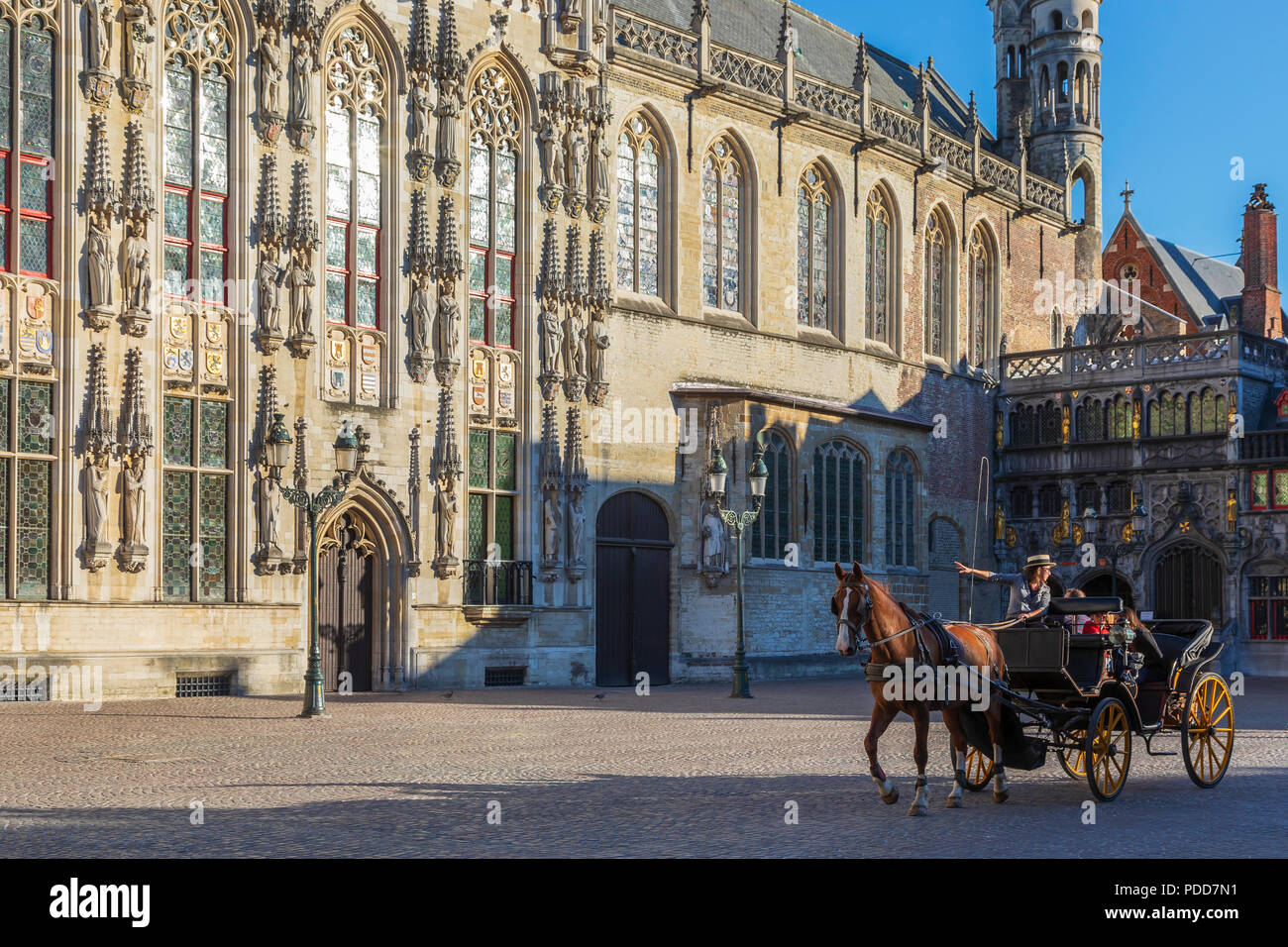 Tourists being taken on a city tour in a horse and trap, passing the old Law courts, Burg, Bruges, Belgium - Stock Image