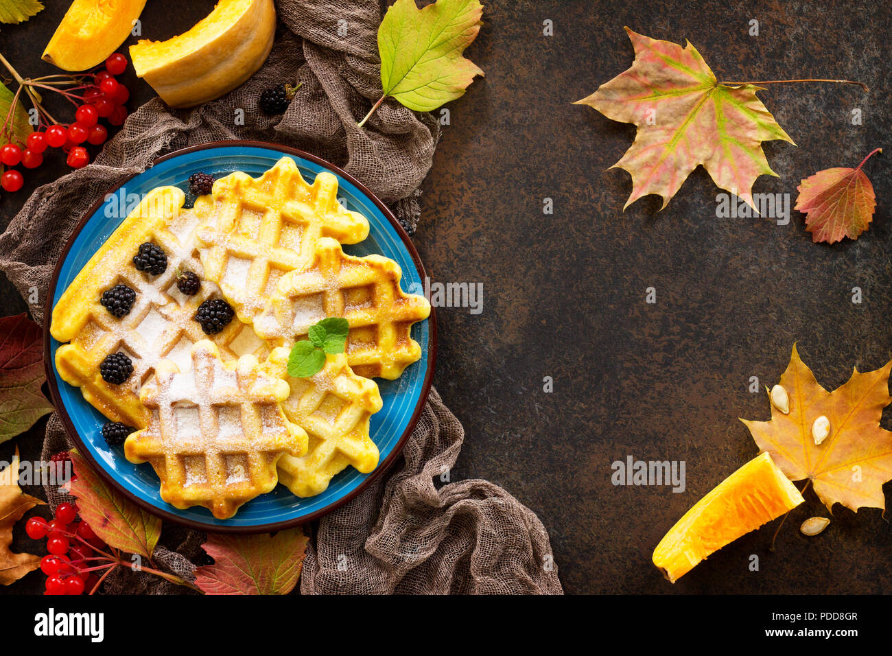 Breakfast table with pumpkin waffles and fresh blackberries on a stone or slate background. Top view flat lay background. Copy space. - Stock Image