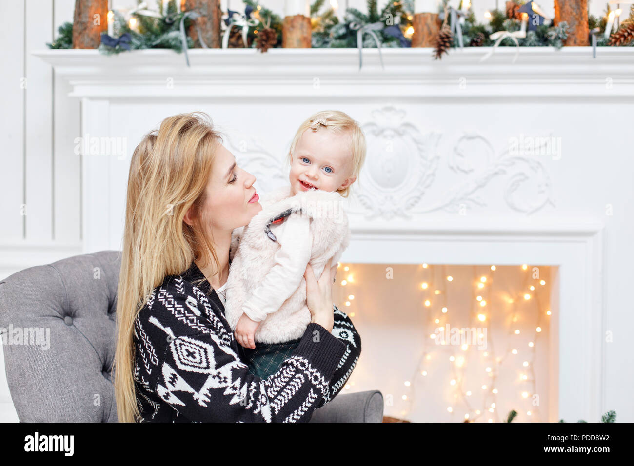 16d79cd3 Cheerful mom embraces her cute baby daughter . Parent and little child  having fun near Christmas tree indoors. Loving family Merry Christmas and  Happy New ...