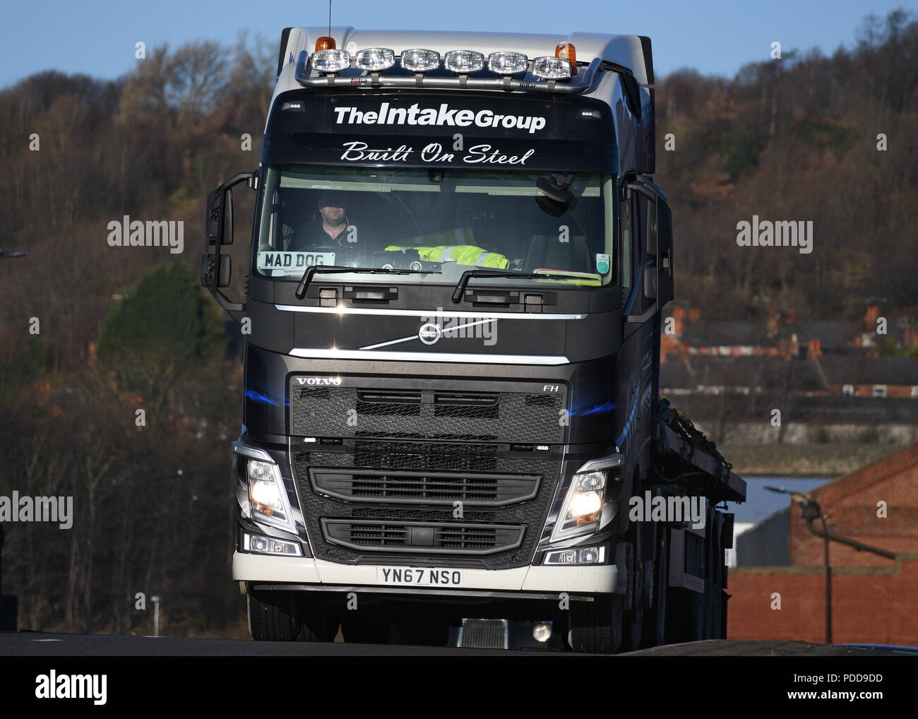 Volvo truck pulling flatbed trailer with steel cargo passes Firth Brown steel Works in Sheffield Stock Photo