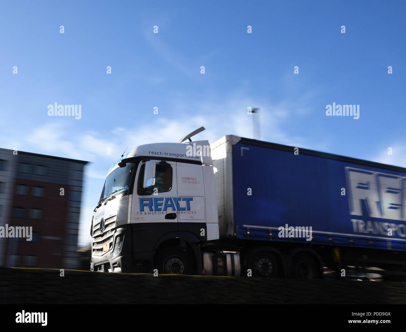 React Transport Mercedes-Benz Actros curtainsider truck driving on an urban dual carriageway Stock Photo