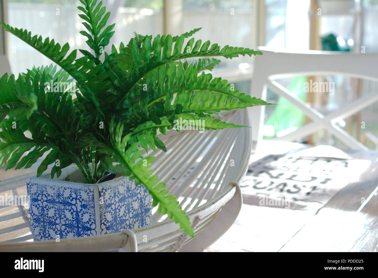 A fake green fern plant in a blue & white plant pot sits in a white cane oval basket. The table decor sits in the centre of a wooden dining table. Stock Photo