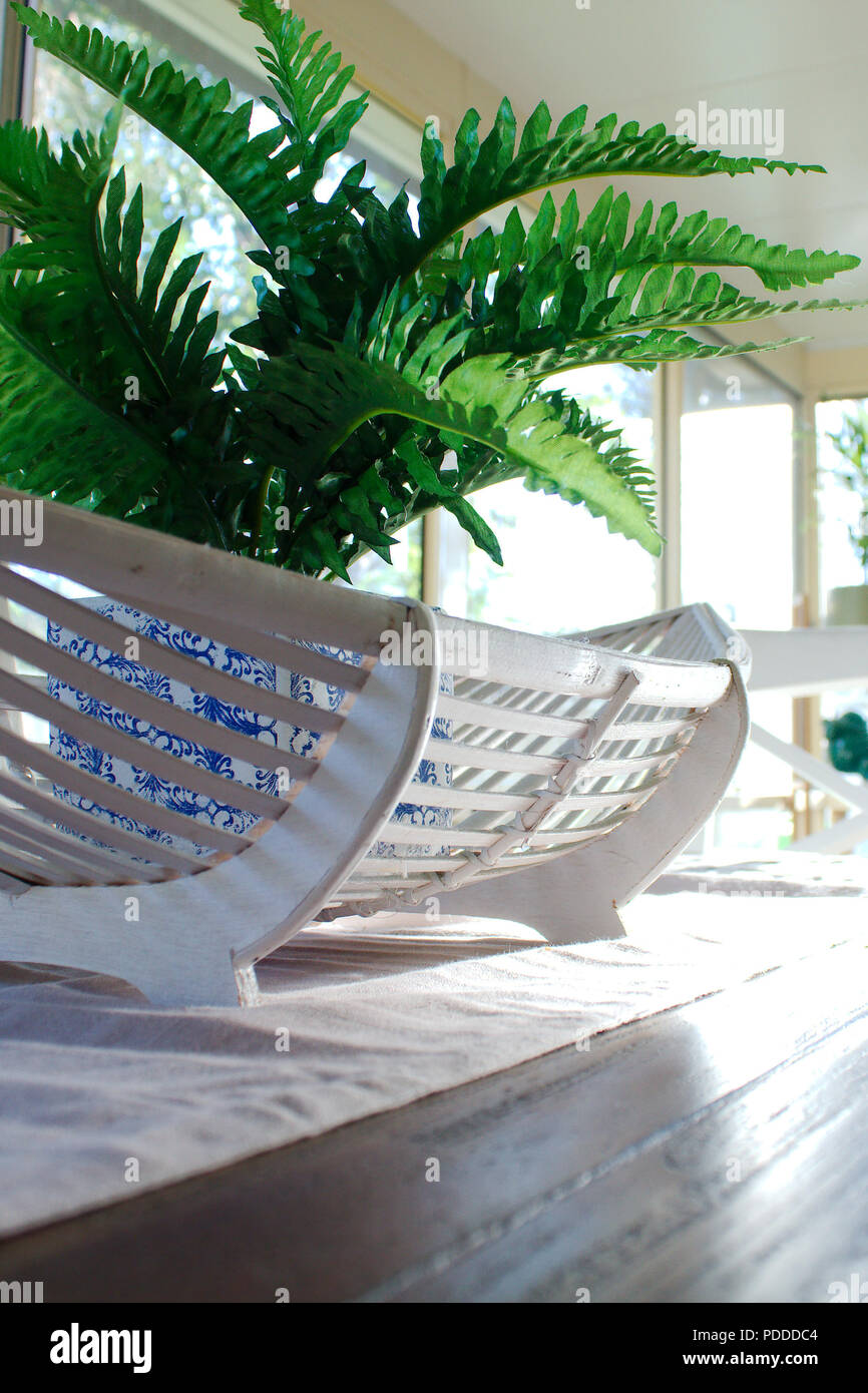 A Fake Green Fern Plant In Blue White Pot Sits Cane Oval Basket The Table Decor Centre Of Wooden Dining