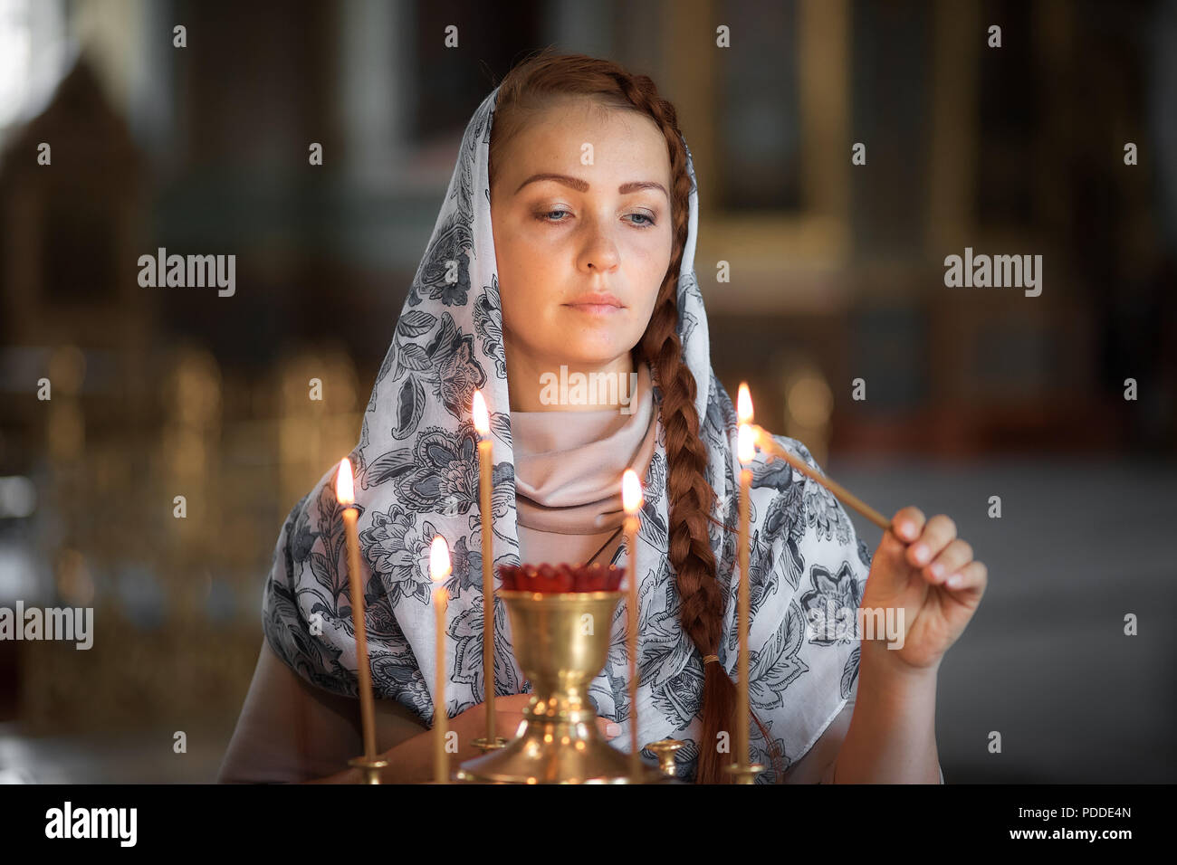 cdefaad936a42 Russian beautiful Caucasian woman with red hair and a scarf on her head is  in the Orthodox Church, lights a candle and prays in front of the icon