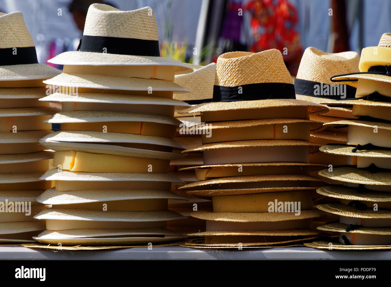 Stacks of straw hats on a market stall on a sunny day - Stock Image