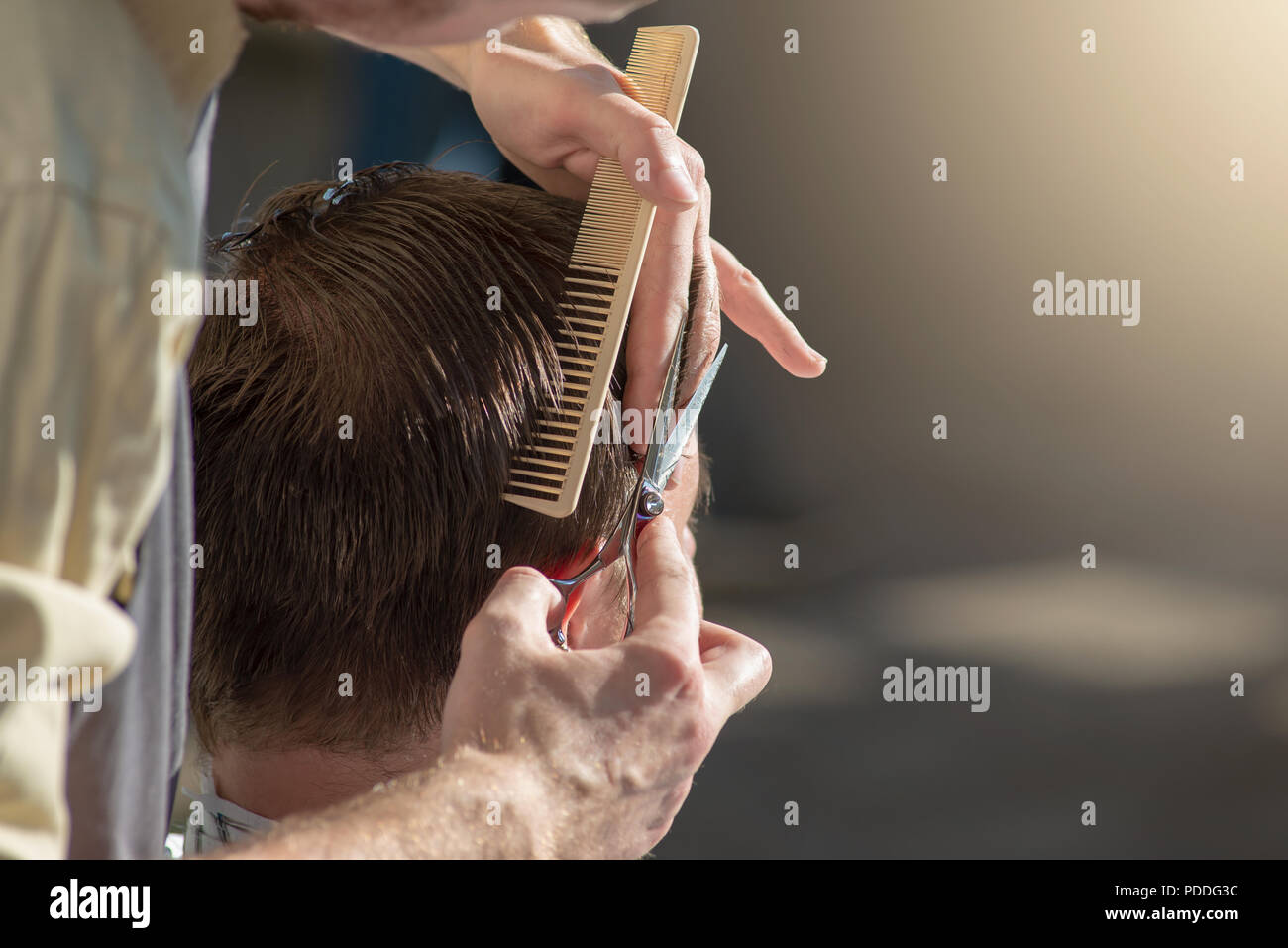 Hands of a hairdresser close-up of scissors and a comb. The barber is cutting a man and doing a haircut. Horizontal photo with text place - Stock Image
