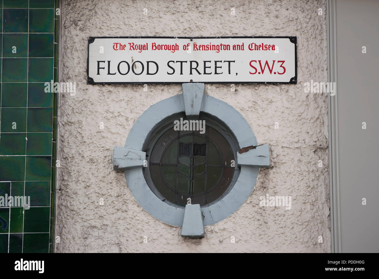 street name sign for flood street, chelsea, london, england, above a porthole window - Stock Image