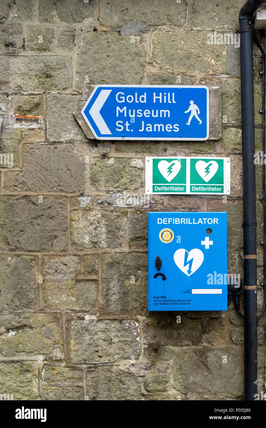 Defibrillator in blue box on stone wall in Shaftesbury Dorset UK - Stock Image