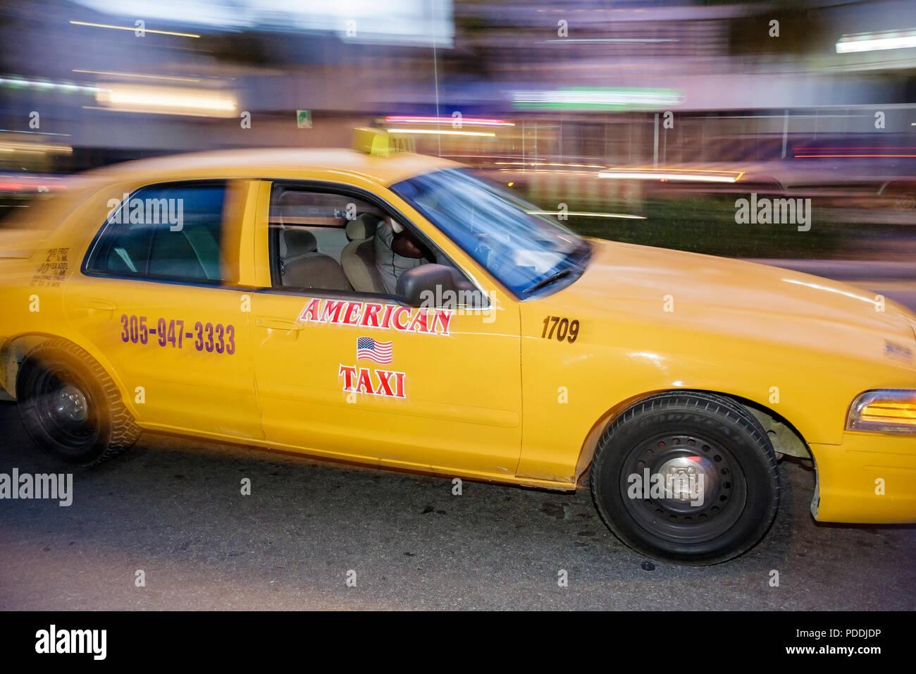 Miami Beach Florida Washington Avenue yellow taxicab taxi cab automobile moving fare ride public transportation driver busines - Stock Image