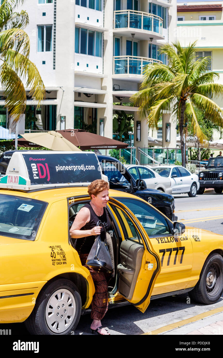 Miami Beach Florida Ocean Drive woman exit gets out yellow taxicab automobile fare ride public transportation driver business - Stock Image