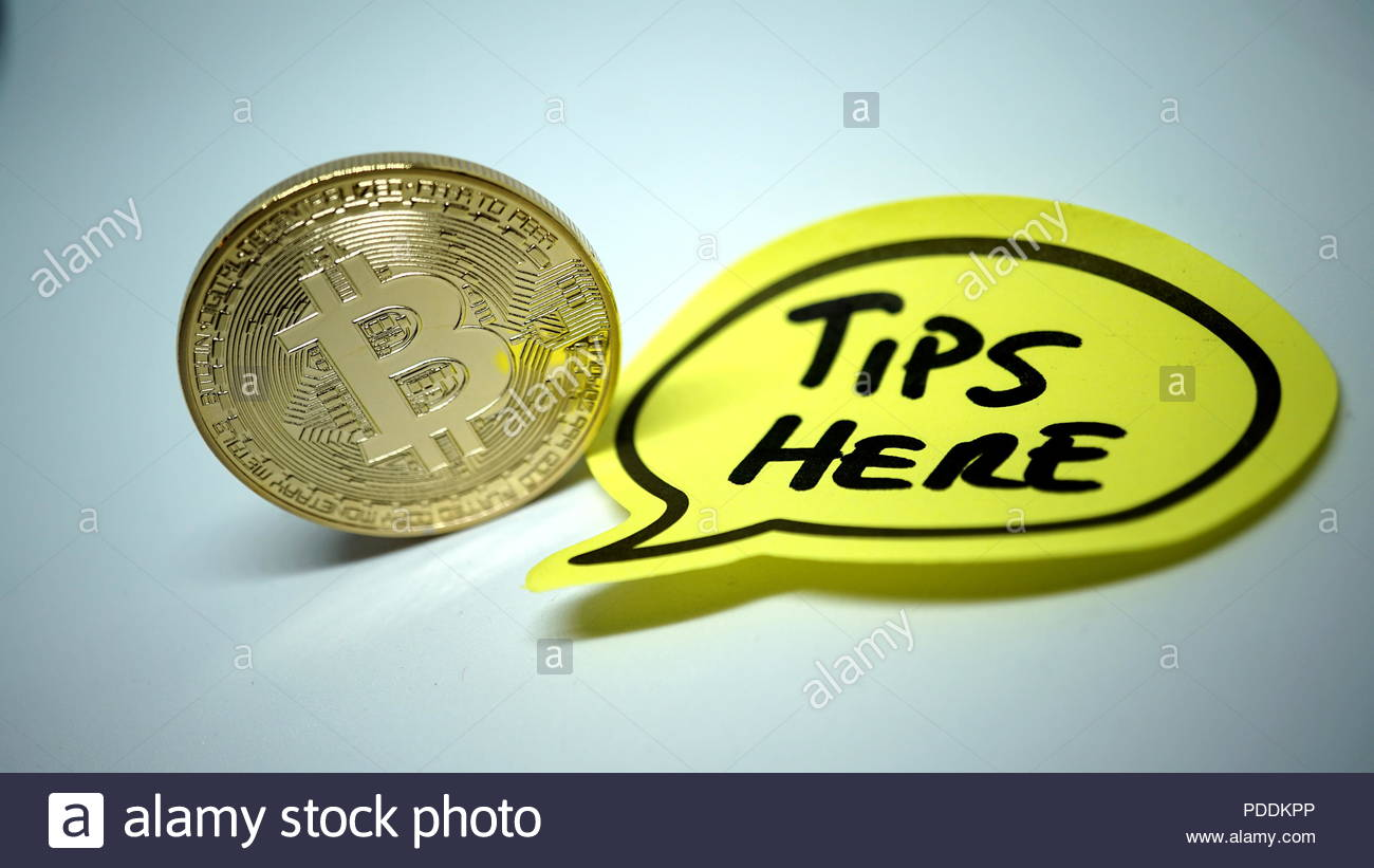 golden bitcoin coin with written tips on yellow sheet in detail - Stock Image