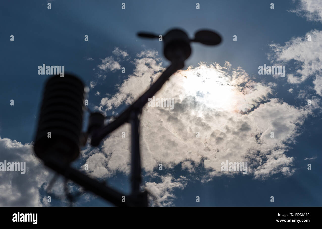 Home weather station on a background of blue sky with the sun behind the clouds. Measurement of temperature, humidity and wind direction - Stock Image
