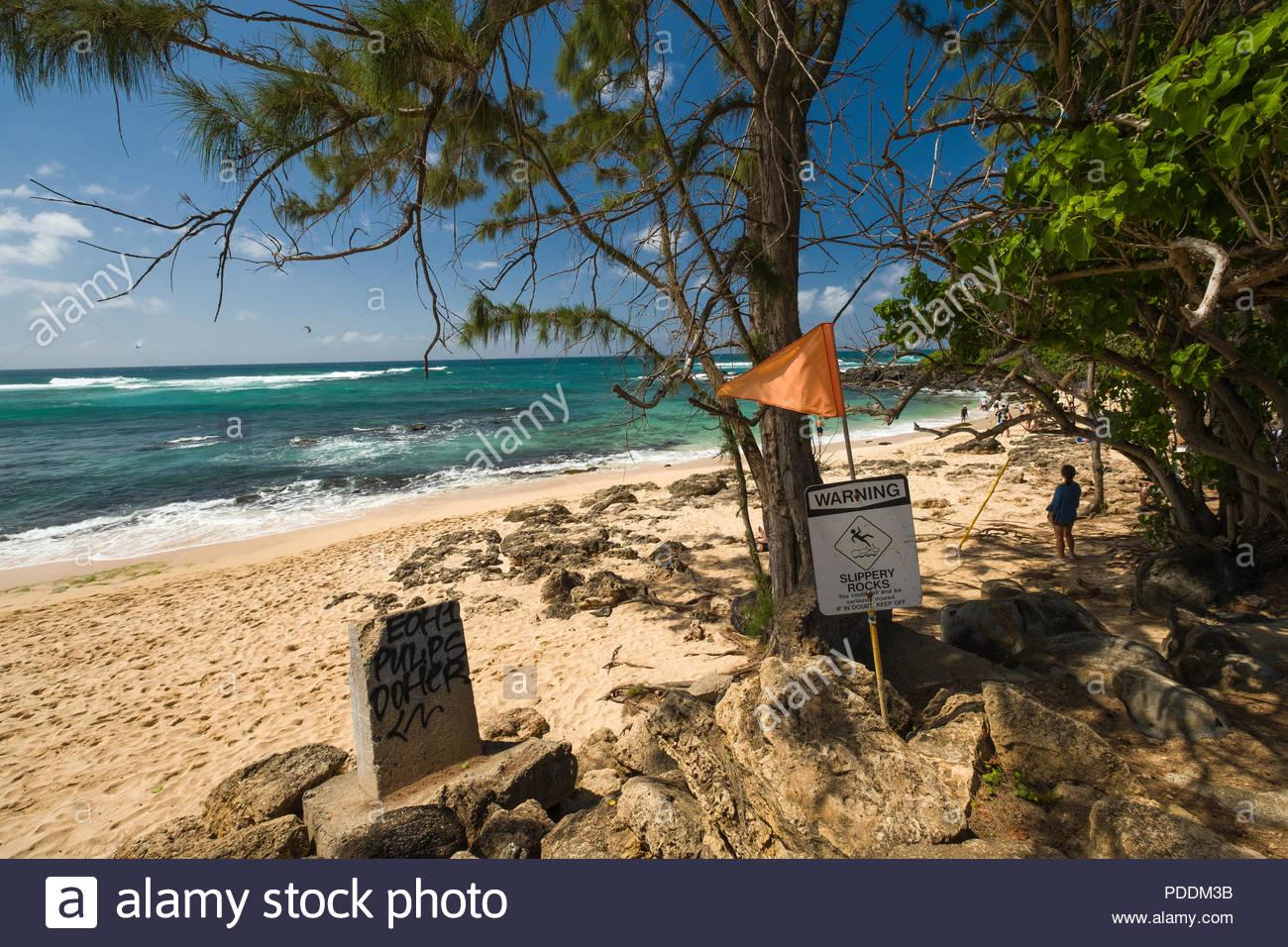 Warning sign for slippery rocks posted at Laniakea Beach, Haleiwa, Oahu, Hawaii, USA - Stock Image