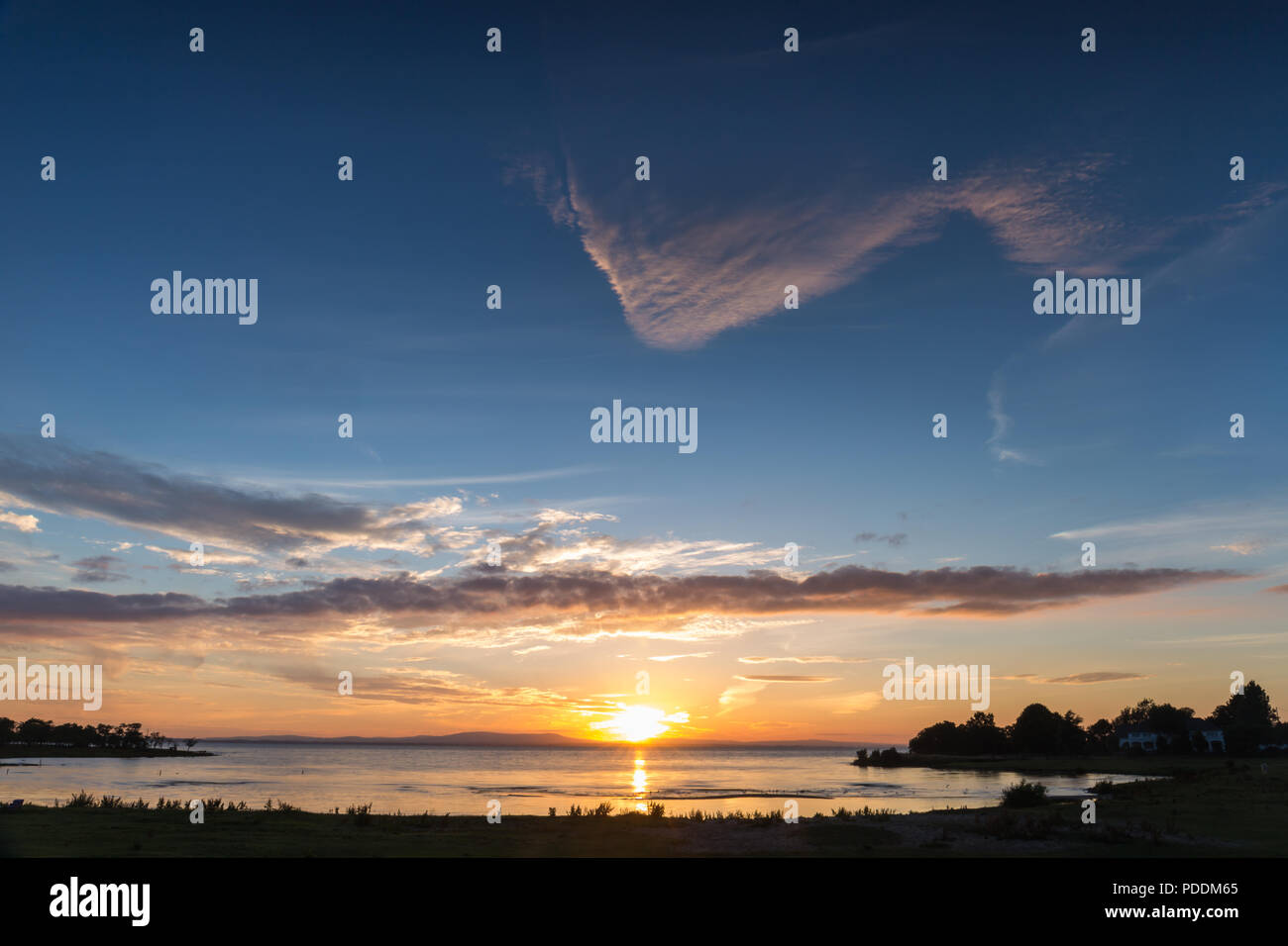 An expansive  beautiful sunset and skyscape over a lake, Lough Neagh, N.Ireland. - Stock Image