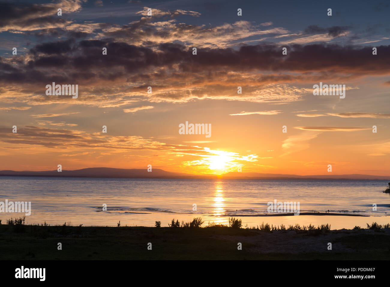 A beautiful sunset and skyscape over a lake, Lough Neagh, N.Ireland. - Stock Image