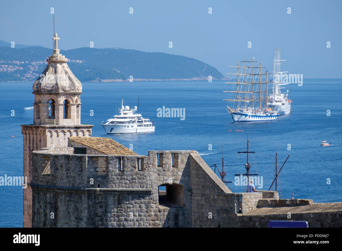 Church tower and the city walls of old town Dubrovnik with sail boats and yachts in the background, Dubrovnik, Croatia, Europe - Stock Image