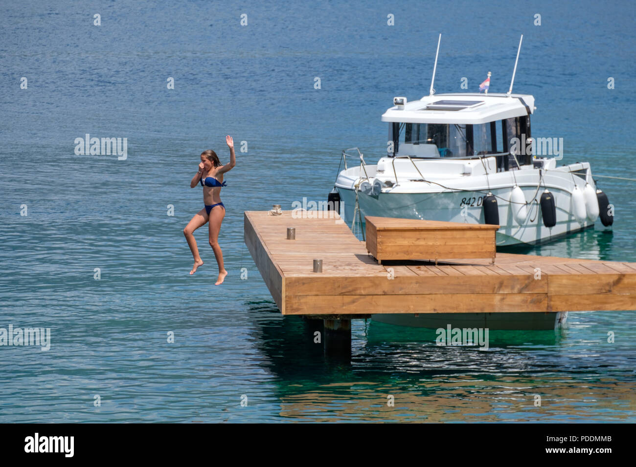 Teenage girl jumping off a dock into the water Stock Photo