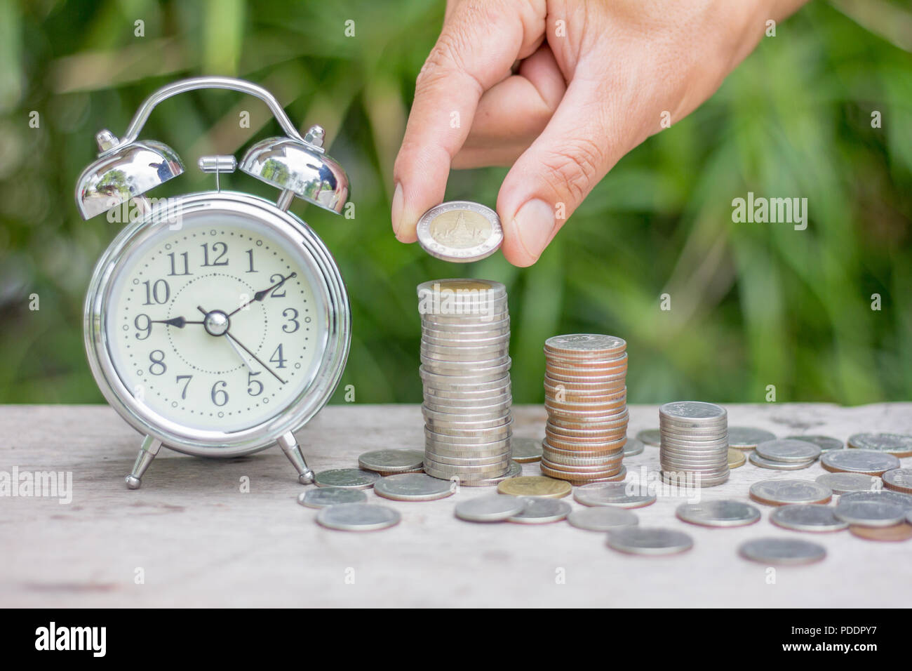 Human hand is putting coin to growing coin stack with clock, Save money for prepare in the future. - Stock Image